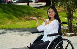 Young brunette woman sitting in wheelchair smiling with positive attitude, outdoors environment, physical recovery Stock Photo