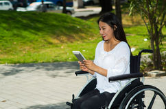 Young brunette woman sitting in wheelchair smiling with positive attitude, using mobile phone, outdoors environment Stock Photos