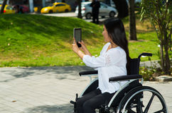 Young brunette woman sitting in wheelchair smiling with positive attitude, using mobile phone, outdoors environment. Physical recovery concept Royalty Free Stock Image