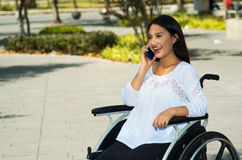 Young brunette woman sitting in wheelchair smiling with positive attitude, using mobile phone, outdoors environment Stock Photography