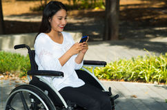 Young brunette woman sitting in wheelchair smiling with positive attitude, using mobile phone, outdoors environment Stock Photo