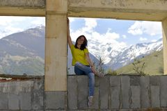 Young woman sitting on the window sill of a destroyed abandoned building in the mountains. stock photography