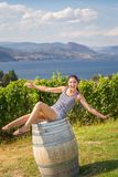 Young brunette woman sitting on a wooden wine barrel in front of a Okanagan vineyard. Young brunette woman sitting on a wooden wine barrel in front of a royalty free stock photos