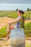 Young brunette woman sitting on a wooden wine barrel in front of a Okanagan vineyard. Young brunette woman sitting on a wooden wine barrel in front of a royalty free stock image