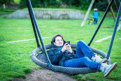 Young brunette woman with smart phone swinging on playground outdoors Royalty Free Stock Photo