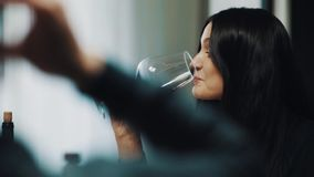 Young brunette woman smiling and drinks wine out glass at dinner table stock footage