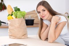 Young brunette woman smiling while sitting at the table near paper bag full of vegetables and fruits. Concept of foo royalty free stock photos