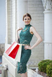 Young brunette woman with some shopping bags. Young beautiful brunette woman with some shopping bags, outdoors summer street royalty free stock photo