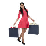 Young brunette woman with some shopping bags. Young beautiful brunette woman in red dress with some shopping bags, isolated on white background Stock Photography