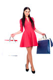 Young brunette woman with some shopping bags. Young beautiful brunette woman in red dress with some shopping bags, isolated on white background Royalty Free Stock Image