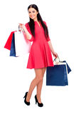 Young brunette woman with some shopping bags. Young beautiful brunette woman in red dress with some shopping bags, isolated on white background Stock Image