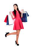 Young brunette woman with some shopping bags. Young beautiful brunette woman in red dress with some shopping bags, isolated on white background Royalty Free Stock Photos