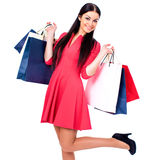Young brunette woman with some shopping bags. Young beautiful brunette woman in red dress with some shopping bags, isolated on white background Stock Images