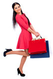 Young brunette woman with some shopping bags. Young beautiful brunette woman in red dress with some shopping bags, isolated on white background Royalty Free Stock Photography