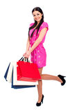Young brunette woman with some shopping bags. Young beautiful brunette woman in red dress with some shopping bags, isolated on white background Stock Photos