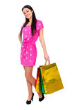 Young brunette woman with some shopping bags. Young beautiful brunette woman in red dress with some shopping bags, isolated on white background Royalty Free Stock Photo