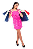 Young brunette woman with some shopping bags. Young beautiful brunette woman in red dress with some shopping bags, isolated on white background Stock Photo