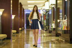 Young brunette woman with some shopping bags in the mall. Young beautiful brunette woman with some shopping bags in the mall stock photos