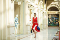 Young brunette woman with some shopping bags in the mall. Young beautiful brunette woman with some shopping bags in the mall royalty free stock photos