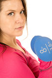 Young brunette woman standing holding blue barbells no smile Royalty Free Stock Photos
