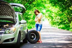 Young brunette woman stands near a silver car on the roadside with a broken wheel Stock Images