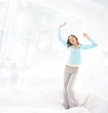 A young brunette woman stretching in a white bed Stock Photos