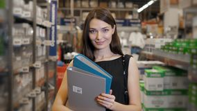 Young brunette woman, student, trainee or employee, smiling while choosing the right book or file from the office in Royalty Free Stock Photo