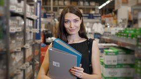 Young brunette woman, student, trainee or employee, smiling while choosing the right book or file from the office in Stock Images