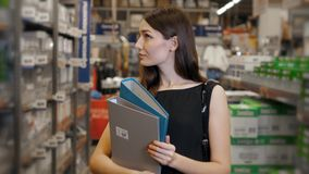 Young brunette woman, student, trainee or employee, smiling while choosing the right book or file from the office in Stock Photo