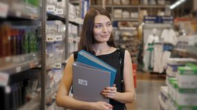 Young brunette woman, student, trainee or employee, smiling while choosing the right book or file from the office in Royalty Free Stock Image