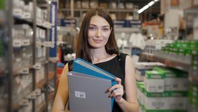 Young brunette woman, student, trainee or employee, smiling while choosing the right book or file from the office in Stock Image