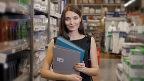 Young brunette woman, student, trainee or employee, smiling while choosing the right book or file from the office in Stock Photos