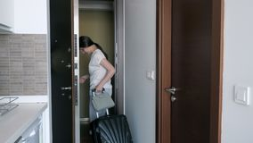 Young woman with suitcase is leaving rented apartments. Young brunette woman with suitcase is leaving rented apartments. She goes out the door and closes it stock video