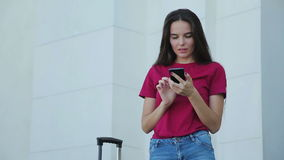 Young brunette woman with suitcase using phone. Young brunette woman with suitcase using smartphone. Female traveller with cellphone stock video footage