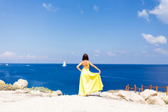 Young brunette woman in summer yellow dress standing on beach and looking to the sea. Stock Photo