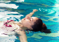 Young brunette woman swimming in the swimming pool at the hotel Royalty Free Stock Photos