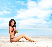 A young brunette woman in a swimsuit drinking a cocktail Royalty Free Stock Photo