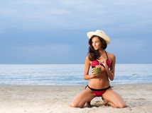 A young brunette woman in a swimsuit drinking a cocktail Royalty Free Stock Images