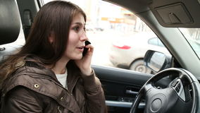 Young brunette woman talking on the mobile phone sitting in the car stock video footage