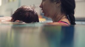 A young brunette woman teaches her child to dive into the water, swimming in the sports pool. Mother and son swim in the. Pool, the child dives into the water stock video