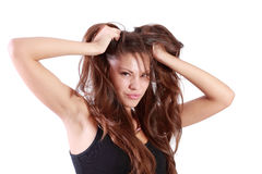 Young brunette woman tears her hair and looks at camera Stock Image