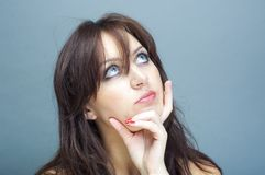 Young brunette woman thinking Royalty Free Stock Images