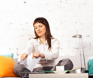 Young brunette woman torning papers. Working at home stock photo
