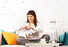 Young brunette woman torning papers. Working at home royalty free stock photo