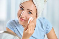 A young brunette woman with a towel wrapped round her head holdi Stock Photography