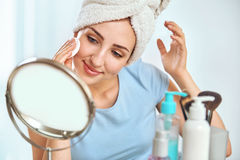 A young brunette woman with a towel wrapped round her head holdi Stock Images