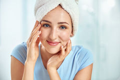 A young brunette woman with a towel wrapped round her head holdi Stock Photo