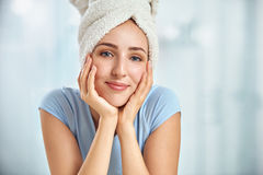 A young brunette woman with a towel wrapped round her head touch Royalty Free Stock Image