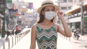 Young brunette woman traveling in Bangkok, Thailand in popular Khao San Road during pandemic Coronavirus. 20s Hispanic
