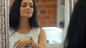 Young brunette woman trying handmade bracelet in front of mirror in the jewelry store royalty free stock photography